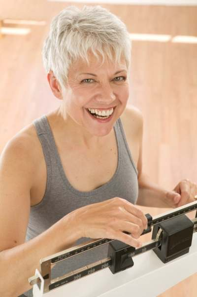 Seven tips for staying young and healthy. Smiling woman using a fitness scale