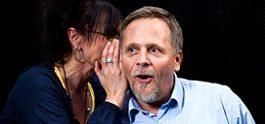 Woman whispering secret in man's ear.